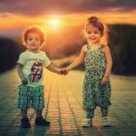 A baby girl and a baby boy walk hand in hand in front of a sunset