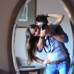 A smilling girl looking in to a mirror with a man huging her from behind holding a camera pointing at the mirror.