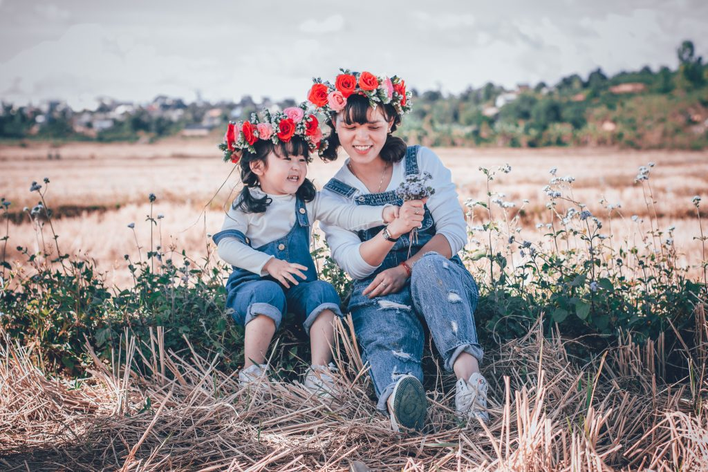Adult women waring jeans and flower in her hair sitting in the gras next to a identical dressed child. Both are smiling happily in the shades on a sunny day outside.