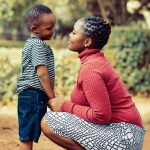 African women in a white and black skirt with a red shirt, kneeling infront of a child in blue shorts and a green t-shirt, both are smiling lovingly