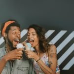 A man and a women about to bite ice cream