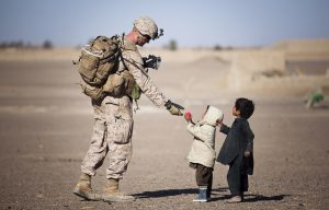 A soldier reaching out to two small kids on a road