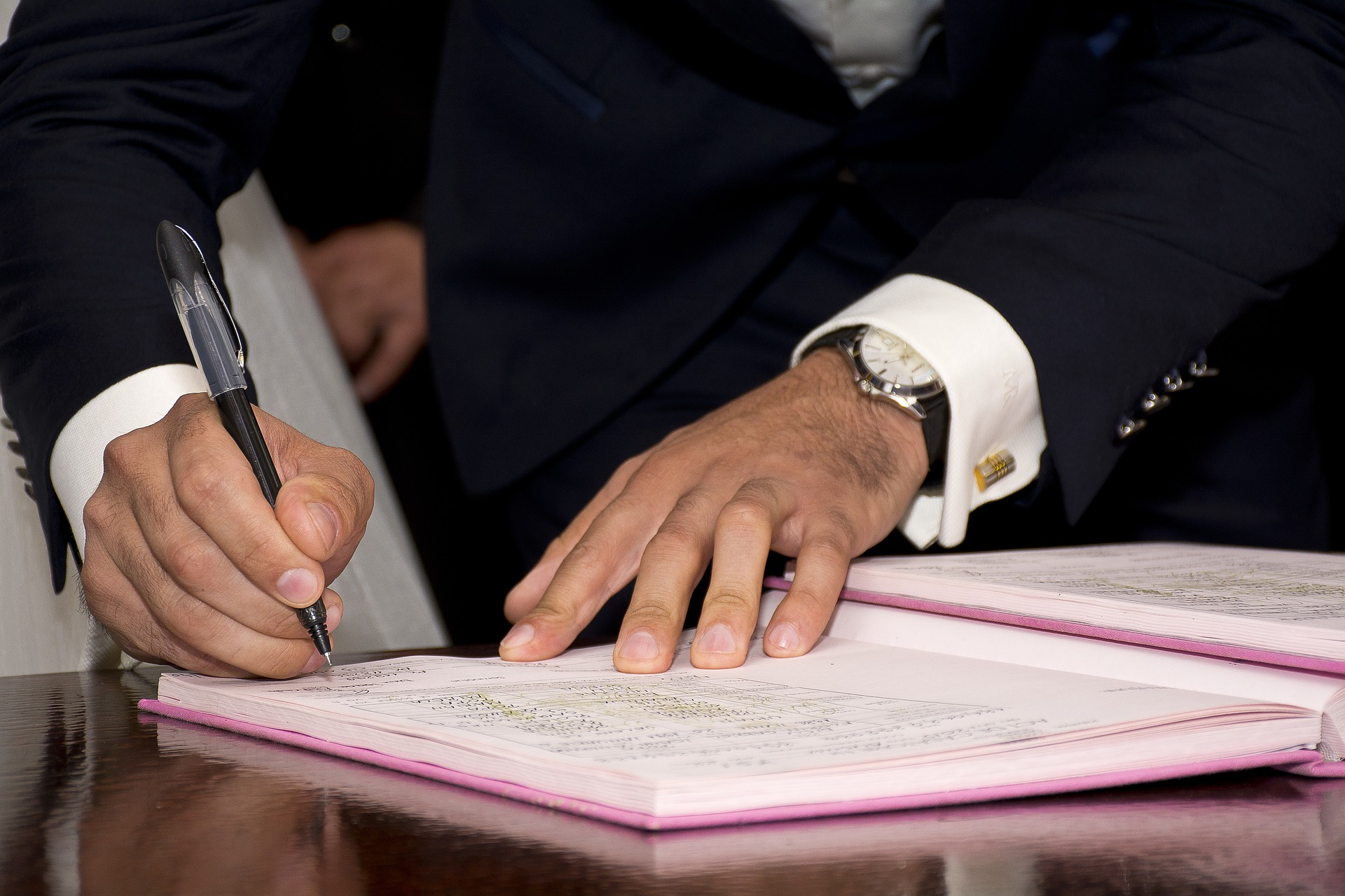Male hands signing a document