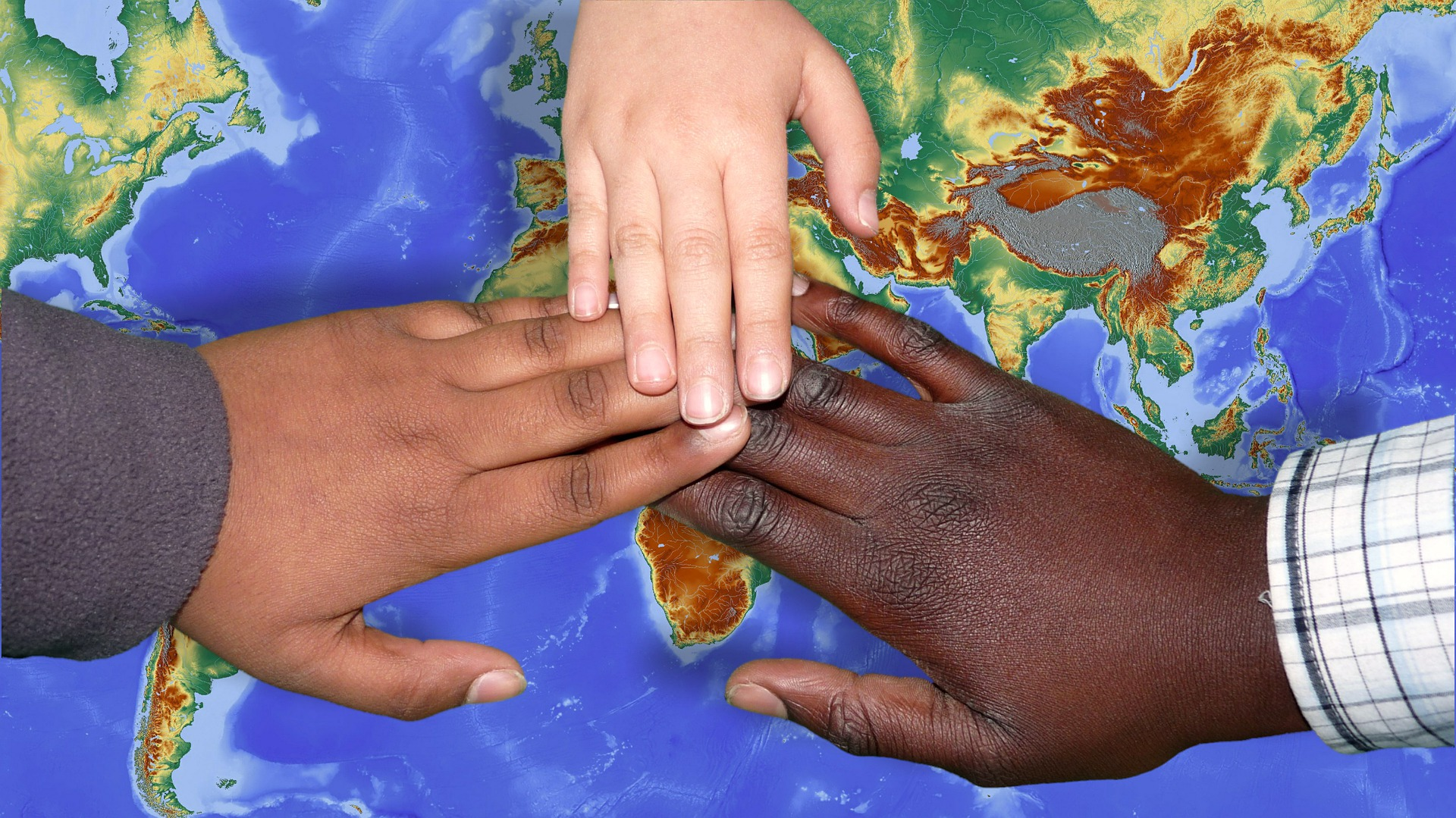 Three children's hands on top of the world