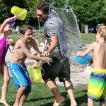Three children and on male adult in a water fight outside in a park