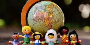 Various small dolls in front of a globe